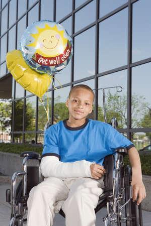 broken arm: African boy with broken arm and balloons in wheelchair
