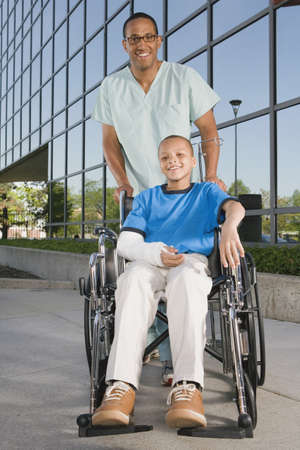 hindering: African boy in wheelchair with nurse in front of hospital