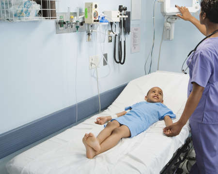 Nurse checking on African boy in hospital bed