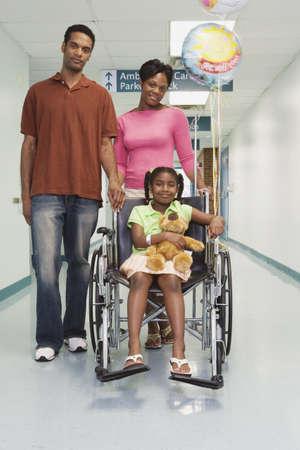 niños africanos: Niña africana sonriente en silla de ruedas con los padres en el hospital