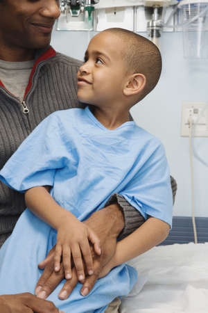solicitous: African boy in hospital gown sitting on father's lap