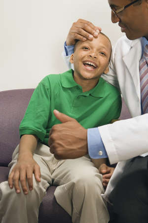 hindering: Doctor giving thumbs up to smiling African boy LANG_EVOIMAGES