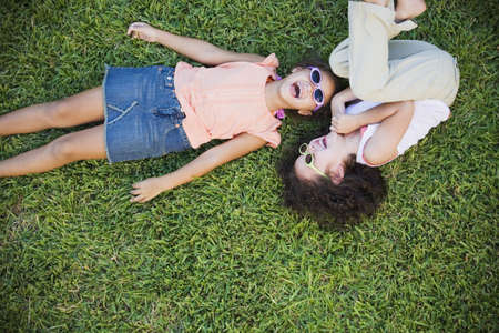 casualness: High angle view of young Hispanic sisters laughing in grass