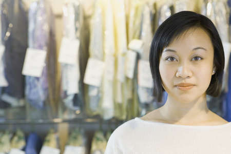 dry cleaning: Portrait of Asian woman in front of dry cleaning LANG_EVOIMAGES
