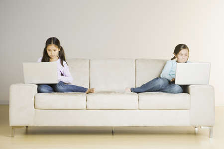 two people only: Two girls looking at laptops on sofa