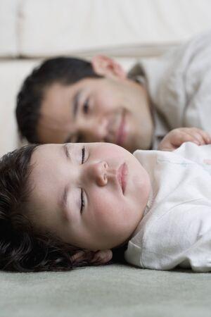 adoring: Hispanic father smiling at sleeping baby
