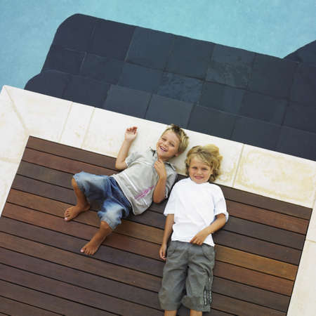 two people only: Two brothers laying next to swimming pool