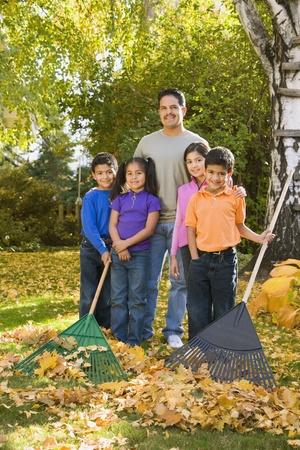 relishing: Portrait of Hispanic family raking leaves