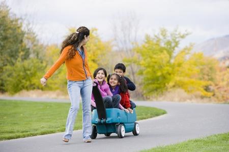hispanic girl: Hispanic mother pulling children in wagon