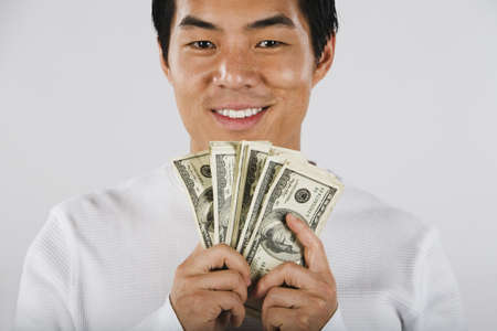 one mid adult man only: Portrait of Asian man holding wad of money LANG_EVOIMAGES