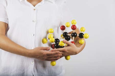 cradling: Asian female scientist cradling chemical model