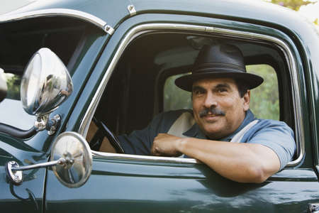 baby boomer: Middle-aged Hispanic man sitting in classic car