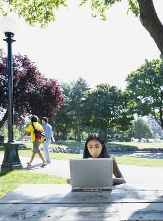 Indian woman typing on laptop outdoors Imagens