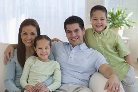 Portrait of Hispanic family on sofa LANG_EVOIMAGES