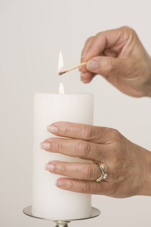 generation gap: Close up of woman lighting candle