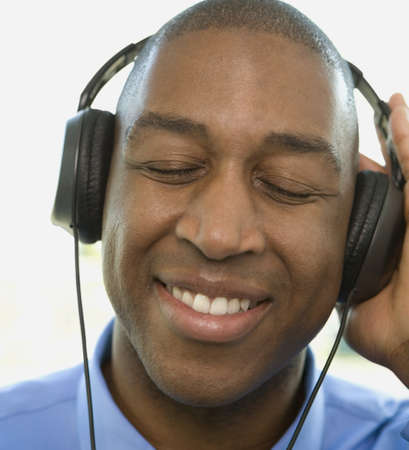 generation gap: African man listening to headphones LANG_EVOIMAGES