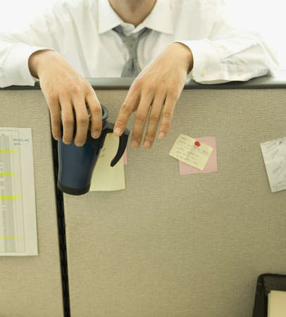 cubicle: Asian businessman leaning on cubicle wall