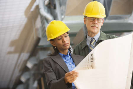 hard hats: Two businesspeople in hard hats looking at blueprints