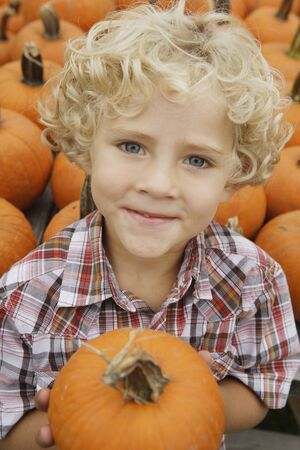 fathering: Portrait of boy holding pumpkin