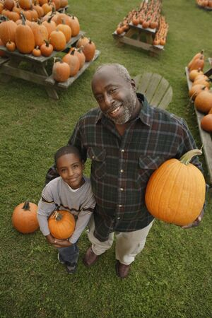 Portrait of African father and son holding pumpkins 스톡 콘텐츠