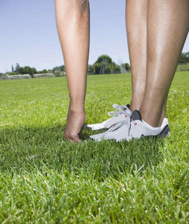 touching toes: African person touching toes in grass