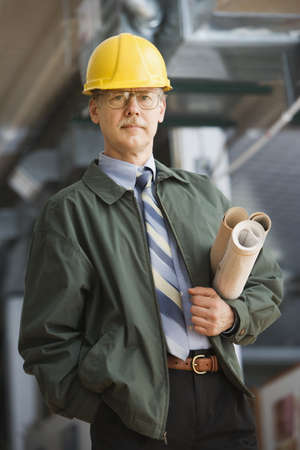 only mid adult women: Businessman in hard hat carrying blueprints LANG_EVOIMAGES