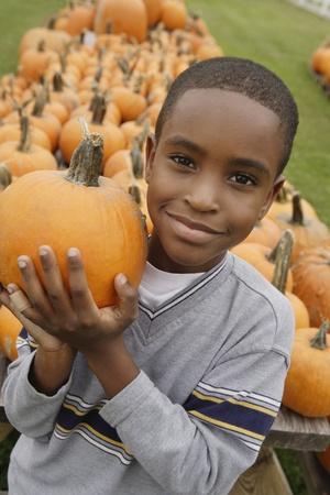 daydreamer: Portrait of African boy holding pumpkin
