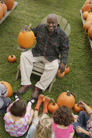 African man talking to children about pumpkins