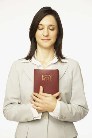 holding bible: Hispanic woman holding Bible