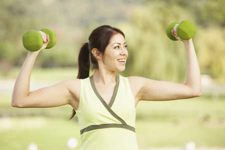 woman lifting weights: Hispanic woman lifting weights outdoors