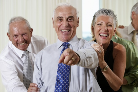 woman s bag: Senior couple at party pointing in surprise