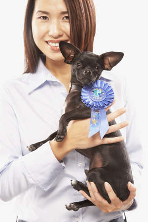 pampered pets: Portrait of Asian woman holding dog with blue ribbon