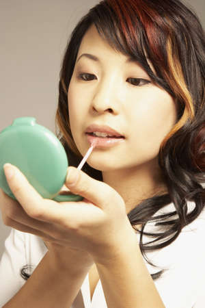 Asian woman applying lip gloss