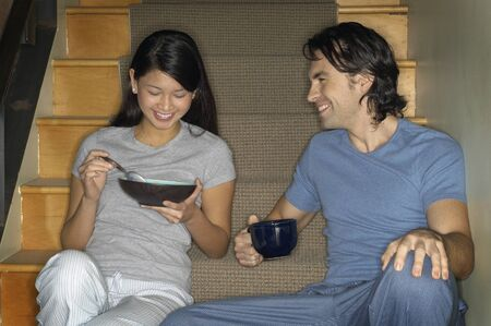 one mid adult man only: Multi-ethnic couple having breakfast on stairs