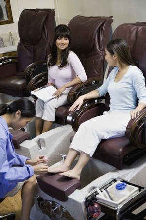 3 persons only: Two women receiving pedicures