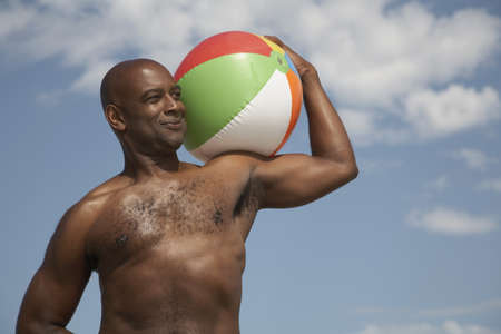 bare waist: Portrait of African man holding beach ball LANG_EVOIMAGES