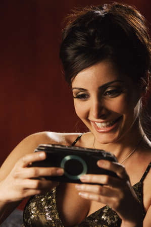 middle eastern woman: Middle Eastern woman playing hand held video game LANG_EVOIMAGES