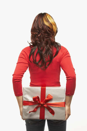 gift behind back: Asian woman holding gift behind back