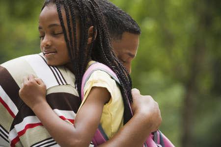 padres: Close up de padre africano y abrazando a su hija LANG_EVOIMAGES