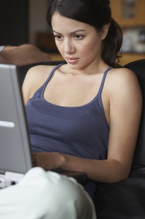 Hispanic woman typing on laptop