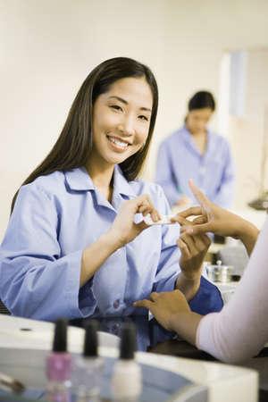 pacific islander ethnicity: Asian nail technician filing client's fingernails LANG_EVOIMAGES