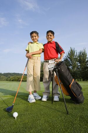 Hispanic brother and sister on golf course 스톡 콘텐츠