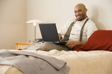 relishing: African businessman typing on laptop