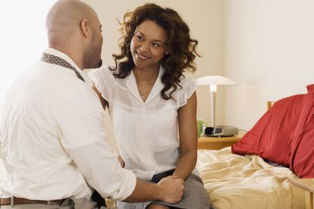 mid adult couple: African couple smiling at each other on bed