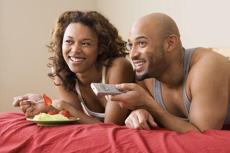 couple bed: Couple africain regarder la t�l�vision au lit LANG_EVOIMAGES