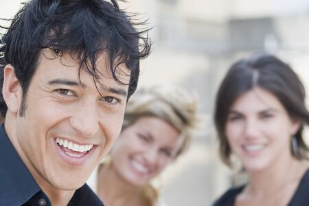 Hispanic man smiling with friends in background