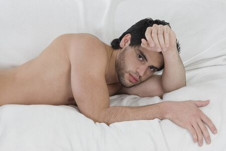 nostril: Bare-chested Hispanic man laying on bed LANG_EVOIMAGES