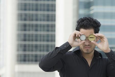 spectating: Hispanic man holding watch over eyes LANG_EVOIMAGES