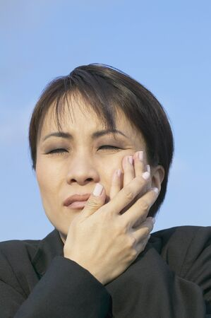 Asian businesswoman with toothache