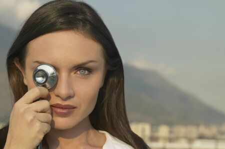 facing away: Young woman holding stethoscope over eye